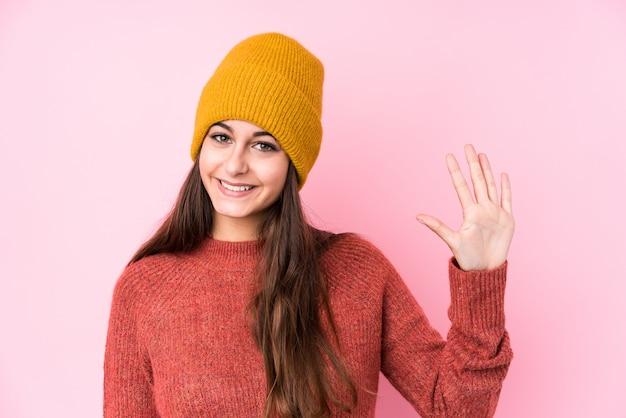 Jonge kaukasische vrouw die een wollen glb draagt dat vrolijk tonend nummer vijf met vingers glimlacht.