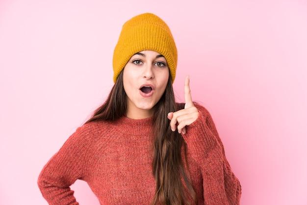 Jonge kaukasische vrouw die een wollen pet draagt die een idee, inspiratieconcept heeft.
