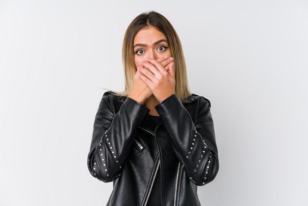 Jonge kaukasische vrouw die een zwart leerjasje draagt dat geschokt mond behandelt met handen.