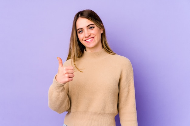 Jonge kaukasische vrouw die en duim glimlacht opheft