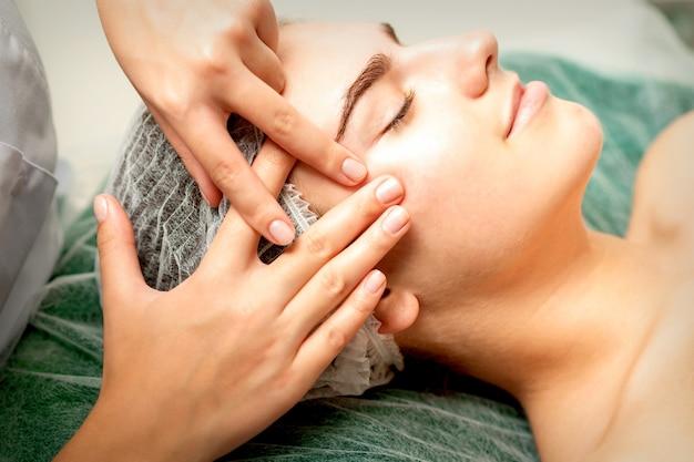 Jonge kaukasische vrouw die gezichtsmassage door schoonheidsspecialisten ontvangt dient de medische salon van de kuur in