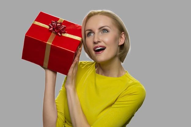 Jonge kaukasische vrouw die haar doos van de verjaardagsgift verheugt. opgewonden jonge vrouw die aan giftdoos luistert.