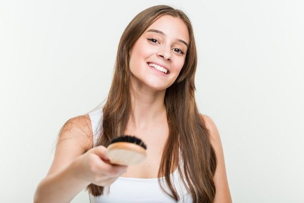 Jonge kaukasische vrouw die haar haar borstelt