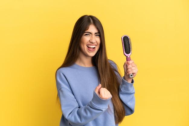 Jonge kaukasische vrouw die haarborstel houdt die op blauwe achtergrond wordt geïsoleerd en een overwinning viert