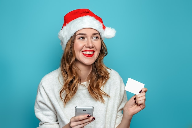 Jonge kaukasische vrouw die in witte sweater en santahoed creditcard en mobiele telefoon houdt die aan de kant kijken en glimlachen geïsoleerd op blauwe muur