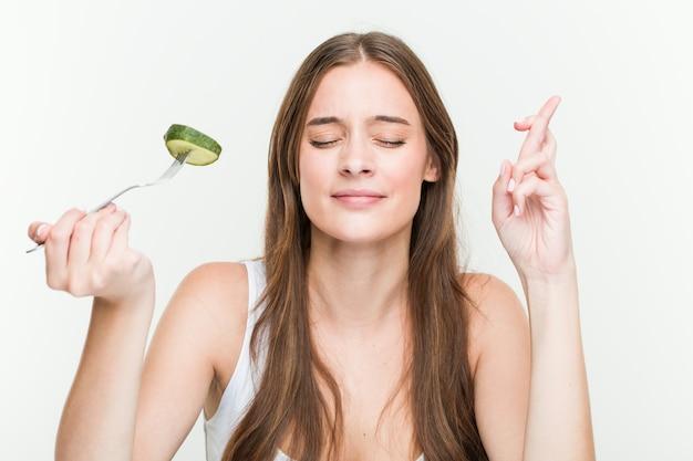 Jonge kaukasische vrouw die komkommer eet die vingers kruist voor het hebben van geluk