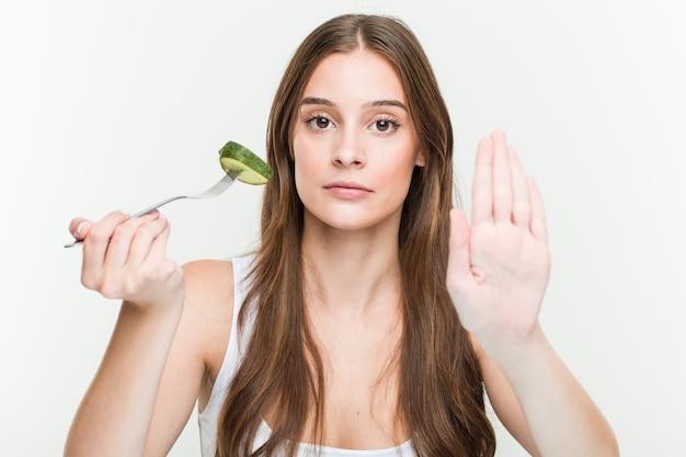 Jonge kaukasische vrouw die komkommer eet die zich met uitgestrekte hand bevindt die eindeteken toont, dat u verhindert.
