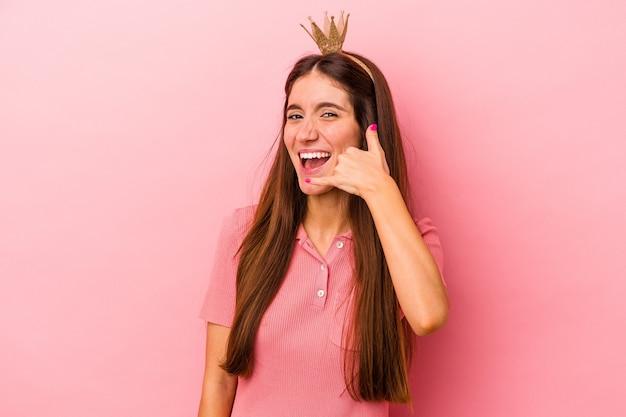 Jonge kaukasische vrouw die kroon draagt die op roze achtergrond wordt geïsoleerd die een mobiel telefoongesprekgebaar met vingers toont.