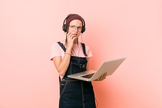 Jonge kaukasische vrouw die laptop bijtende vingernagels houdt, zenuwachtig en zeer bezorgd.