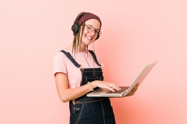 Jonge kaukasische vrouw die laptop gelukkig, glimlachend en vrolijk houdt.