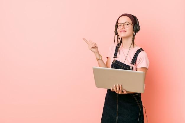 Jonge kaukasische vrouw die laptop houdt glimlachend vrolijk wijzend met weg wijsvinger.