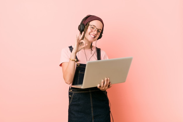 Jonge kaukasische vrouw die laptop vrolijk en zeker houdt die ok gebaar toont.