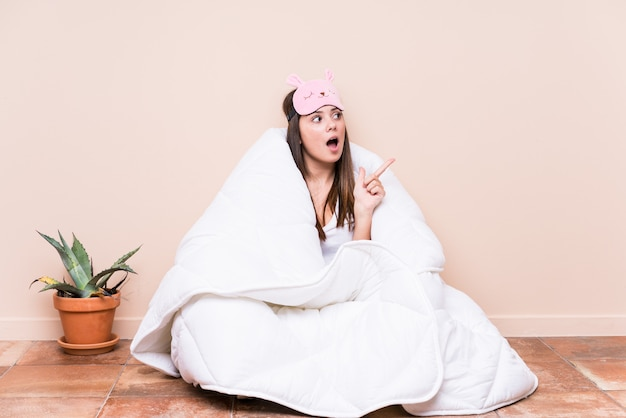 Jonge kaukasische vrouw die met een dekbed rust dat aan de kant richt