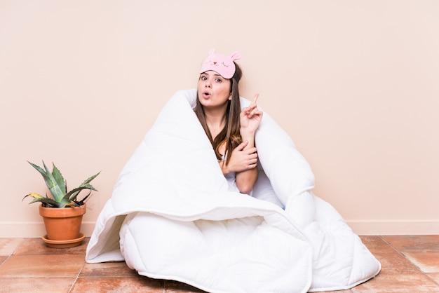 Jonge kaukasische vrouw die met een dekbed rust dat één of ander groot idee, concept heeft creativiteit.