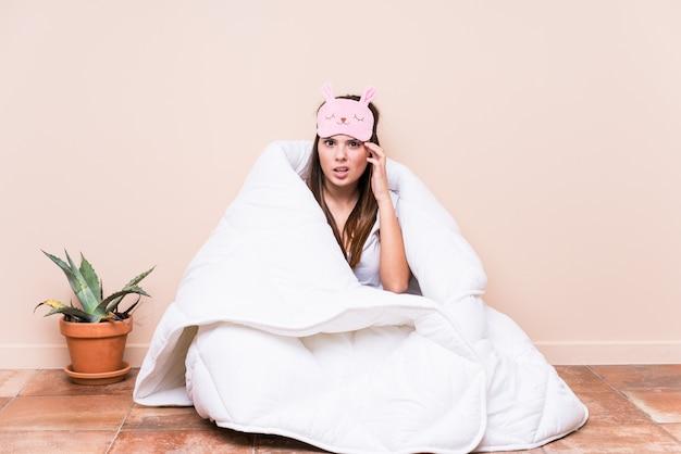 Jonge kaukasische vrouw die met een dekbed rust dat een teleurstellingsgebaar met wijsvinger toont.