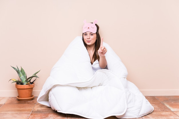 Jonge kaukasische vrouw die met een dekbed rust dat nummer één met vinger toont.