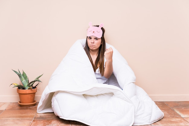 Jonge kaukasische vrouw die met een dekbed rust dat vuist toont aan met agressieve gelaatsuitdrukking.