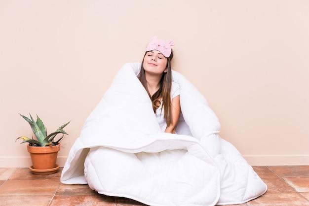 Jonge kaukasische vrouw die met een dekbed rust die van het bereiken van doelstellingen en doeleinden droomt