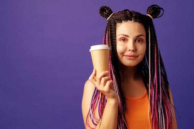 Jonge kaukasische vrouw die met kleurrijke lange cornrows een kop van koffie houdt tegen purpere achtergrond