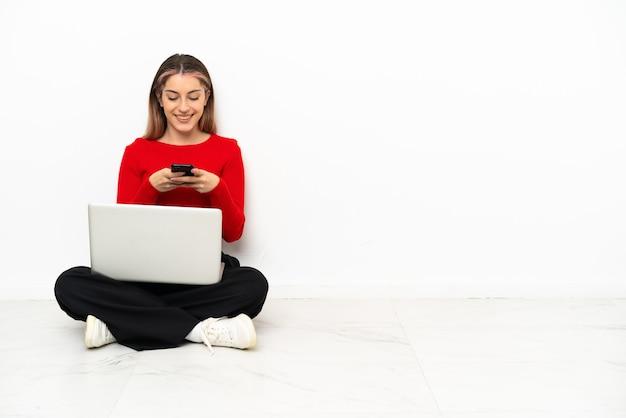 Jonge kaukasische vrouw die met laptop op de vloer zit die een bericht met mobiel verzendt