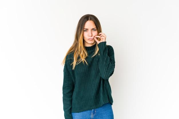 Jonge kaukasische vrouw die met vingers op lippen een geheim houdt.