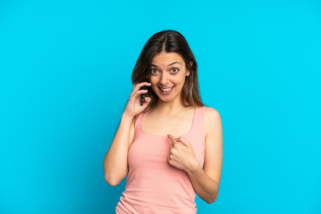 Jonge kaukasische vrouw die mobiele telefoon gebruikt die op blauwe achtergrond met verrassingsgelaatsuitdrukking wordt geïsoleerd