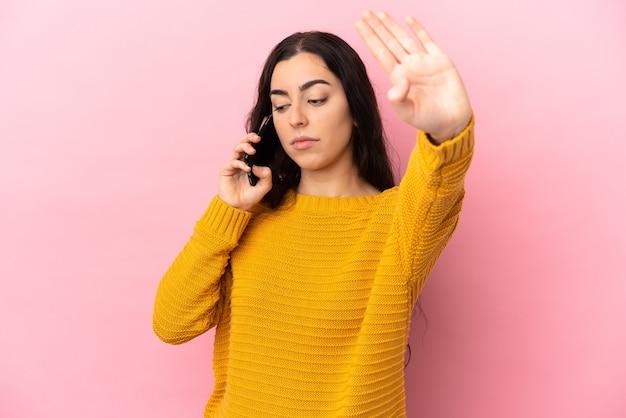 Jonge kaukasische vrouw die mobiele telefoon gebruikt die op roze achtergrond wordt geïsoleerd en een stopgebaar maakt en teleurgesteld is?