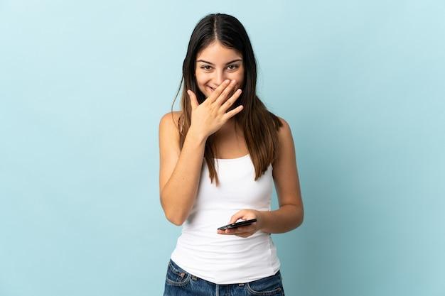 Jonge kaukasische vrouw die mobiele telefoon met behulp van die op blauwe muur gelukkig en het glimlachen behandelt mond met hand gebruiken