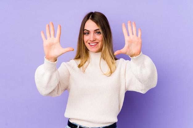 Jonge kaukasische vrouw die nummer tien met handen toont.