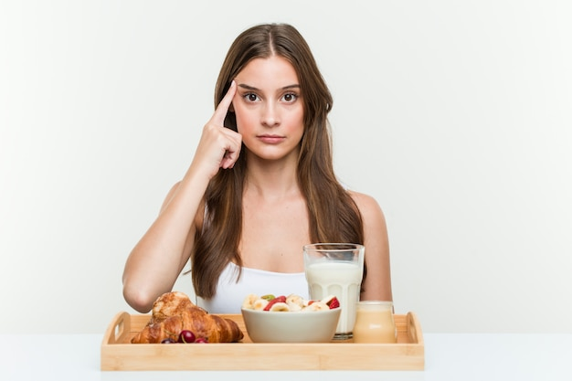 Jonge kaukasische vrouw die ontbijt heeft die zijn tempel met vinger richten, geconcentreerd denken, ontask.