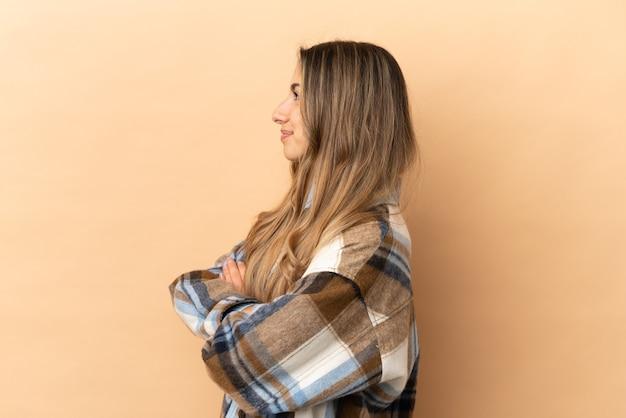 Jonge kaukasische vrouw die op beige achtergrond in zijpositie wordt geïsoleerd