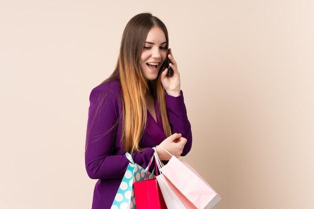 Jonge kaukasische vrouw die op beige de boodschappentassen van de muurholding wordt geïsoleerd en een vriend met haar celtelefoon roept