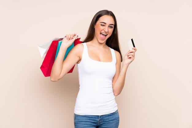Jonge kaukasische vrouw die op beige holdings het winkelen zakken en een creditcard wordt geïsoleerd