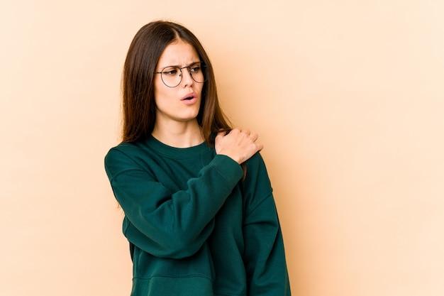 Jonge kaukasische vrouw die op beige muur wordt geïsoleerd die een schouderpijn heeft.