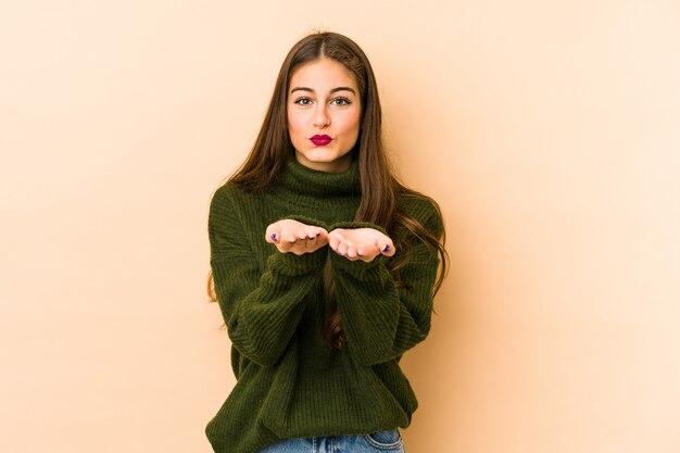 Jonge kaukasische vrouw die op beige vouwende lippen wordt geïsoleerd en palmen houdt om luchtkus te verzenden.