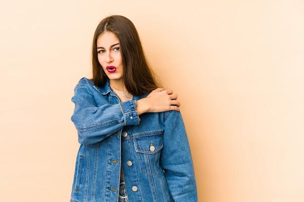 Jonge kaukasische vrouw die op beige wordt geïsoleerd dat schouderpijn heeft.