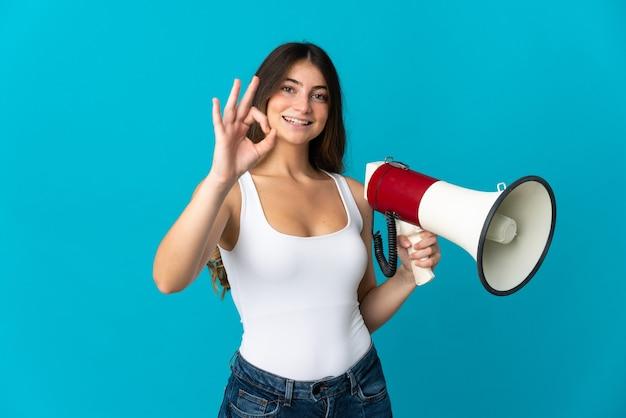 Jonge kaukasische vrouw die op blauw wordt geïsoleerd dat een megafoon houdt en ok teken met vingers toont