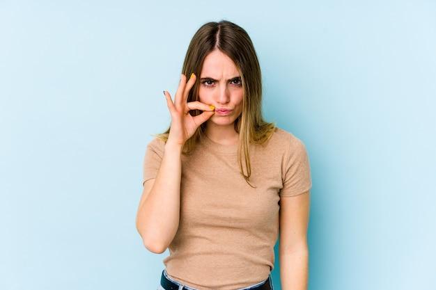 Jonge kaukasische vrouw die op blauwe achtergrond met vingers op lippen wordt geïsoleerd die een geheim houden.