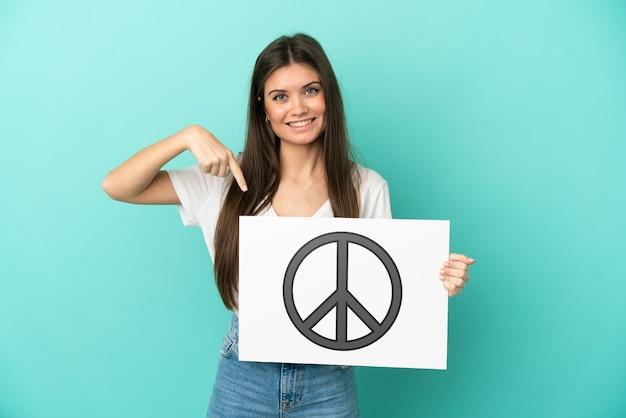 Jonge kaukasische vrouw die op blauwe achtergrond wordt geïsoleerd die een aanplakbiljet met vredessymbool houdt en het richt