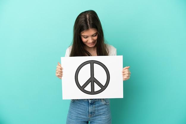 Jonge kaukasische vrouw die op blauwe achtergrond wordt geïsoleerd die een aanplakbiljet met vredessymbool houdt