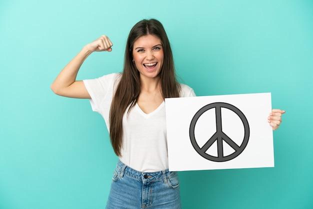 Jonge kaukasische vrouw die op blauwe achtergrond wordt geïsoleerd die een plakkaat met vredessymbool houdt en sterk gebaar doet