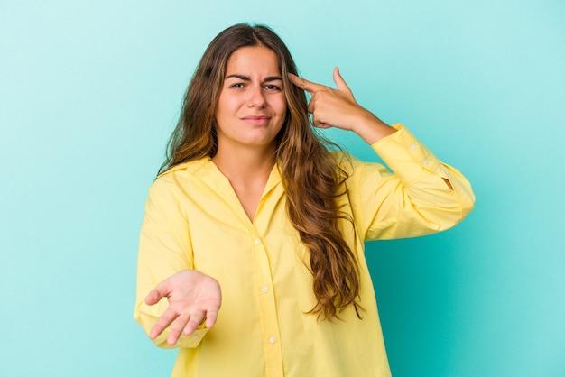 Jonge kaukasische vrouw die op blauwe achtergrond wordt geïsoleerd die een product bij de hand houdt en toont.