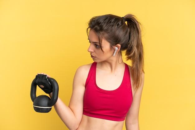 Jonge kaukasische vrouw die op blauwe achtergrond wordt geïsoleerd die gewichtheffen met kettlebell maakt