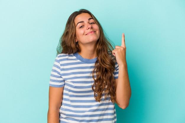 Jonge kaukasische vrouw die op blauwe achtergrond wordt geïsoleerd die nummer één met vinger toont.