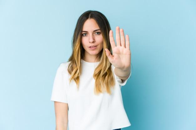 Jonge kaukasische vrouw die op blauwe achtergrond wordt geïsoleerd die zich met uitgestrekte hand bevindt die stopbord toont, dat u verhindert.