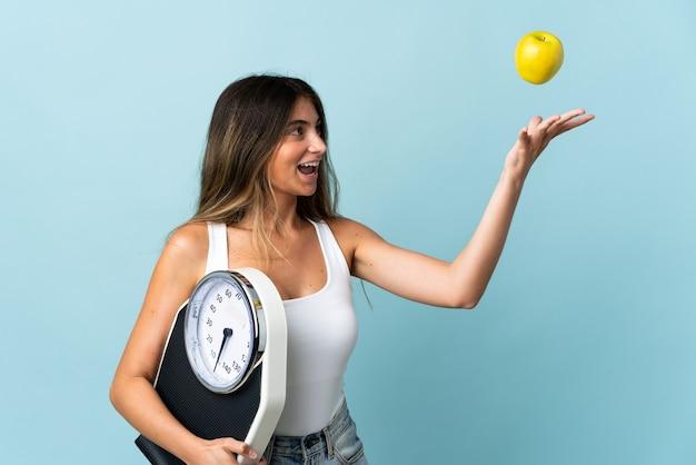 Jonge kaukasische vrouw die op blauwe muur met weegmachine en met een appel wordt geïsoleerd