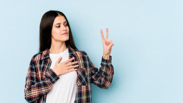 Jonge kaukasische vrouw die op blauwe muur wordt geïsoleerd die een eed aflegt, die hand op borst zet.