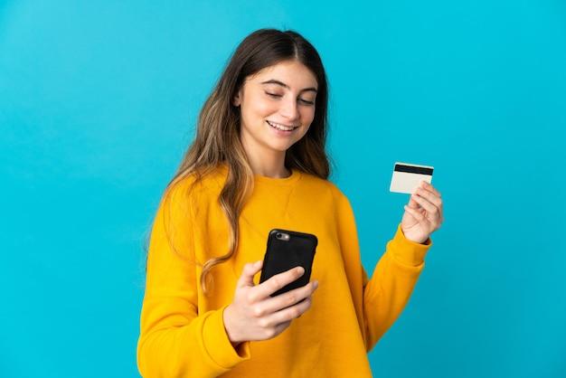Jonge kaukasische vrouw die op blauwe muur wordt geïsoleerd die met mobiel met een creditcard koopt