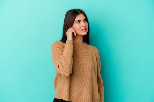 Jonge kaukasische vrouw die op blauwe muur wordt geïsoleerd die oren behandelt met handen