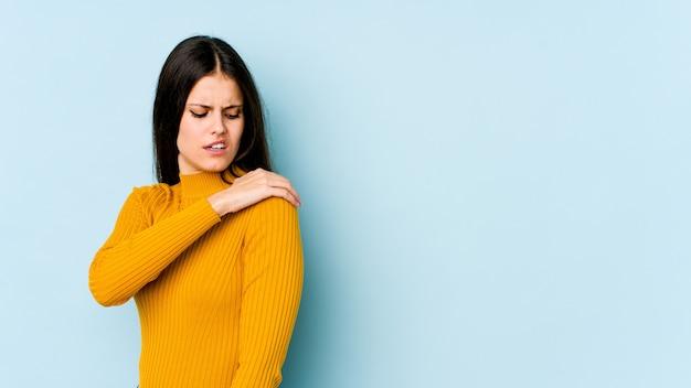 Jonge kaukasische vrouw die op blauwe muur wordt geïsoleerd die schouderpijn heeft.